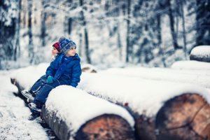 Kids having fun in forest on winter day. Resting on snow covered tree trunks.